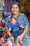 Mayan kvinna i traditionella kläder som rymmer en docka Royaltyfria Foton