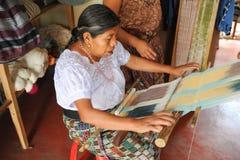 Mayan kvinna som väver garner på San Juan la laguna Arkivfoto