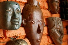 Mayan Masks. Wooden Mayan masks on display (and for sale) on a brick wall in an indoor market in Mazatlan, Mexico Stock Photography