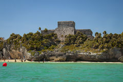 Mayan Ruins in Tulum, Mexico. Tulum, Mexico - February 25, 2017: view of ruins of archeological Mayan site of Tulum, with beach goers on the shore stock photo