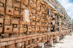 Mayan Temple in Kabah Yucatan Mexico. Detail of the facade of a Mayan temple with a wall of stone chac masks, the rain god and its prominent nose and eyes, in Royalty Free Stock Photos