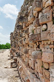 Mayan Temple in Kabah Yucatan Mexico. Detail of the facade of a Mayan temple with a wall of stone chac masks, the rain god and its prominent nose and eyes, in Stock Photo