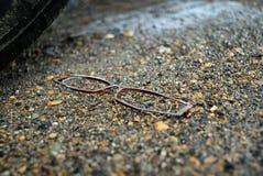 Eyeglasses laying on the wet ground. stock photo
