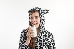Maybe a hot bath and a glass of milk. Young pretty woman in spotted cow pajama holding glass of milk. Adorable girl royalty free stock photo