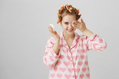 Maybe I do not see but hear. Portrait of cute funny european female in hair curlers and nightwear wiping off mascara Stock Photos