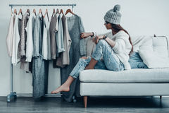 Maybe this one?. Thoughtful young woman in casual wear choosing the dress while sitting on the couch at home near her clothes hanging on the racks Stock Photo
