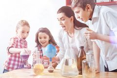 Scared group of elementary students and tutor during scientific experiment. Maybe it was the wrong decision. Frightened little chemists and their teacher Royalty Free Stock Images