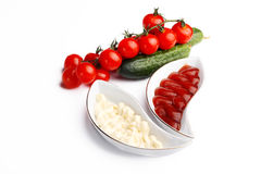 Mayonnaise, ketchup and vegetables on white Stock Image
