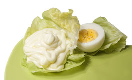 Mayonnaise on lettuce. Mayonnaise arrangement on a lettuce leaf with boiled egg on a green plate, isolated on white royalty free stock image