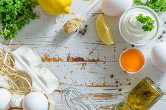 Mayonnaise sauce and ingredients on wood background. Copy space Stock Photos