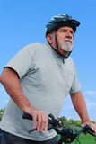 Mayor activo que monta una bici Imagen de archivo