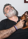 Mayor atractivo con la barba blanca que juega con el perro basset Foto de archivo libre de regalías