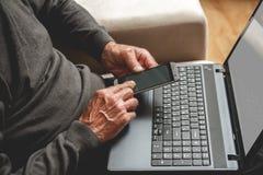 Mayor con el teléfono y el ordenador portátil Imagenes de archivo