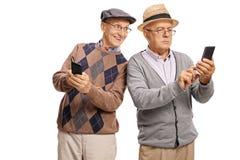 Mayor con un teléfono que mira el teléfono de su amigo Imágenes de archivo libres de regalías