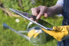 Mayor de la mujer que cultiva un huerto que usa una tableta digital en su GA Fotografía de archivo