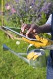 Mayor de la mujer que cultiva un huerto que usa una tableta digital en su GA Imagenes de archivo