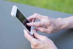 Mayor de la mujer que usa un teléfono móvil en jardín Foto de archivo libre de regalías