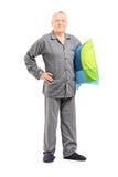 Mayor en la camisa de dormir que sostiene una almohada Imágenes de archivo libres de regalías