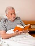 Mayor en la clínica de reposo para leer el libro en cama Fotos de archivo