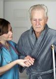 Mayor en las muletas asistidas por su enfermera Imagen de archivo