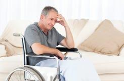 Mayor en su sillón de ruedas que tiene un dolor de cabeza Foto de archivo libre de regalías