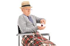 Mayor en una silla de ruedas que sostiene un manojo de píldoras Imágenes de archivo libres de regalías
