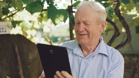 Mayor feliz emotionaly usando la tableta en el jardín 4K metrajes