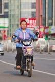 Mayor femenino en una e-bici con las señalizaciones de la tienda en el fondo, Pekín, China Imágenes de archivo libres de regalías