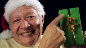 Mayor masculino emocionado con Santa Cap Points At Gift almacen de video