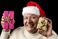 Mayor masculino feliz que muestra dos presentes envueltos fotografía de archivo libre de regalías