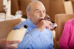 Mayor que bebe un vidrio de vino rojo en restaurante Imagen de archivo