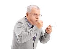 Mayor que fuma un cigarro y toser Imagenes de archivo