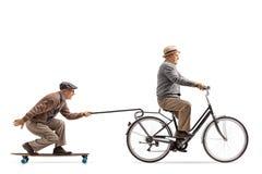 Mayor que monta una bici con otro montar a caballo mayor un longboard y Imágenes de archivo libres de regalías