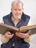 Mayor que sostiene la biblia de familia. Fotografía de archivo