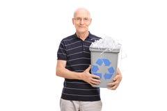 Mayor que sostiene una papelera de reciclaje llena de papel destrozado Fotografía de archivo libre de regalías