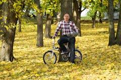 Mayor y su bicicleta en parque del otoño imágenes de archivo libres de regalías