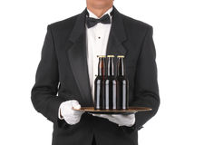 Mayordomo con las botellas de cerveza en la bandeja imagenes de archivo