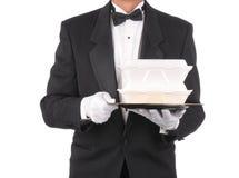Mayordomo con los envases de alimento para llevar en la bandeja Imagenes de archivo
