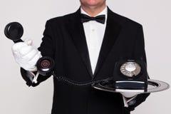 Mayordomo que le da un teléfono Fotos de archivo libres de regalías