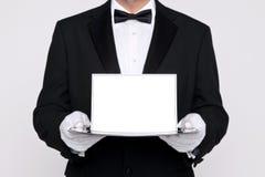Mayordomo que sostiene una tarjeta en blanco sobre una bandeja de plata Foto de archivo libre de regalías