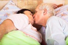 Mayores cariñosos que se besan en cama Imagenes de archivo