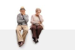 Mayores deprimidos que se sientan en un panel Fotos de archivo libres de regalías