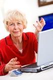 Mayores: Mujer mayor confundida por el ordenador portátil Imágenes de archivo libres de regalías
