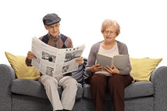 Mayores que leen un periódico y un libro fotografía de archivo libre de regalías