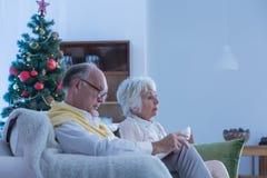 Mayores que se sientan en el sofá durante la Navidad fotos de archivo libres de regalías