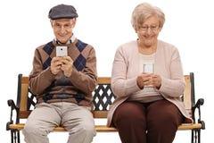 Mayores que se sientan en un banco y que miran sus teléfonos imagenes de archivo