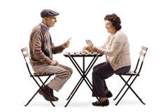 Mayores que se sientan en una tabla y los naipes foto de archivo libre de regalías