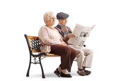 Mayores que sientan en banco con uno de ellos el periódico de la lectura fotografía de archivo libre de regalías
