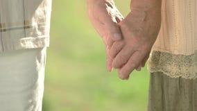 Mayores que tocan suavemente las manos juntas almacen de metraje de vídeo