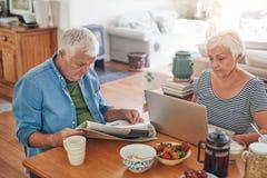 Mayores que usan un ordenador portátil y leyendo el periódico sobre el desayuno Imágenes de archivo libres de regalías